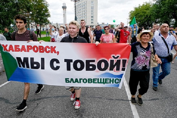 "KHABAROVSK, RUSSIA - JULY 25, 2020: People carry a sign reading ""Khabarovsk, we are with you! Blagoveshchensk"" as they take part in an unauthorized rally in support of former Khabarovsk Territory Governor Sergei Furgal, arrested on suspicion of organizing murders of entrepreneurs and a murder attempt back in 2004-2005. Rallies in support of Furgal are held in Russia's Khabarovsk Territory from July 11. Dmitry Morgulis/TASSРоссия. Хабаровск. Шествие участников несогласованной акции в поддержку бывшего губернатора Хабаровского края Сергея Фургала, который был задержан по делу об организации убийств и попытки убийства. В Хабаровском крае несогласованные акции из-за ареста Фургала проходят с 11 июля. Дмитрий Моргулис/ТАСС"